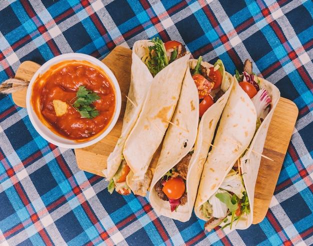Традиционные мексиканские тако; соус сальса с мясом и овощами на разделочной доске