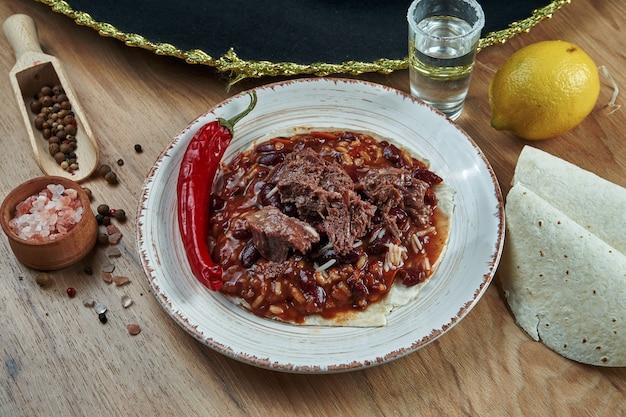 Традиционные мексиканские тако с фасолью, перцем чили, говядиной в белой керамической пластине на деревянном столе. вкусный говяжий буррито с чили кон карне в кукурузных тако