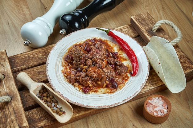 豆、チリペッパー、木製のテーブルに白いセラミックプレートで牛肉と伝統的なメキシコのタコス。トウモロコシのタコスのおいしいチリコンカルネビーフブリトー