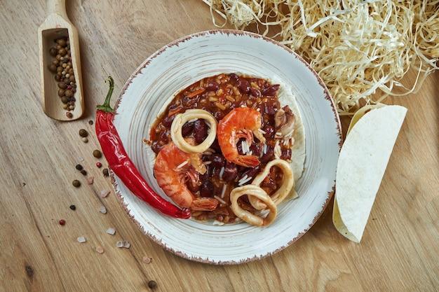 Традиционные мексиканские тако с фасолью, перцем чили, креветками и кальмарами в белой керамической плите на деревянном столе. вкусный чили кон карне морепродукты буррито в кукурузных тако