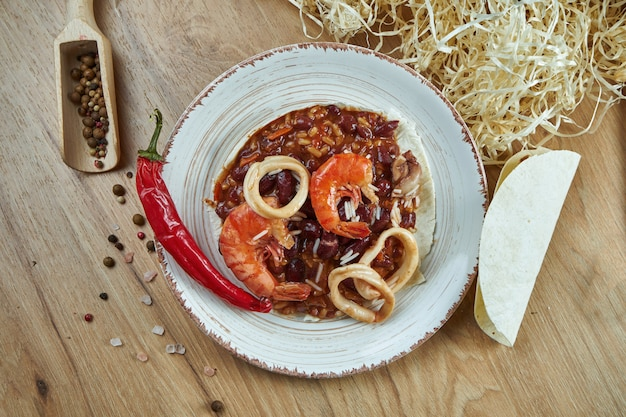 Traditional mexican tacos with beans, chili peppers, shrimp and squid in white ceramic plate on wooden table. tasty chili con carne seafood burritos in corn tacos