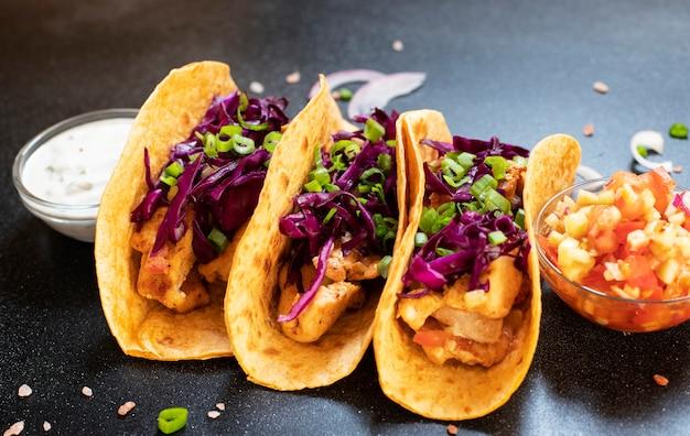 닭고기, 구운 야채, 양파 및 자주색 양배추를 곁들인 전통적인 멕시코 타코는 흰색과 붉은 소스와 양파 링과 함께 제공됩니다. 확대. 어두운 배경. 공간 복사