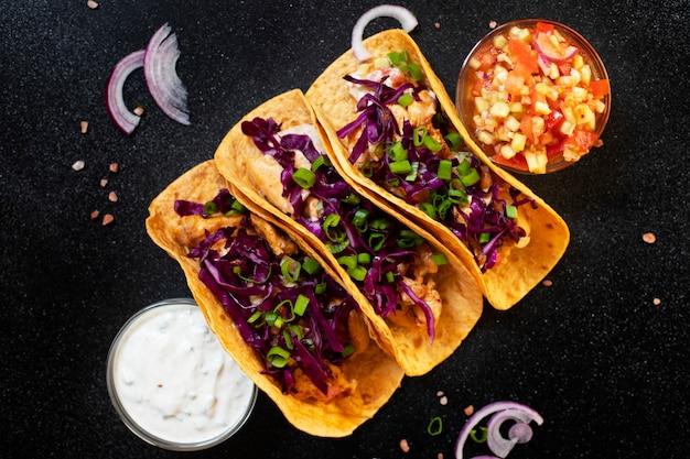닭고기, 구운 야채, 양파 및 자주색 양배추와 함께 전통적인 멕시코 타코는 흰색과 빨간색 소스와 함께 제공됩니다. 평면도. 어두운 배경. 공간 복사