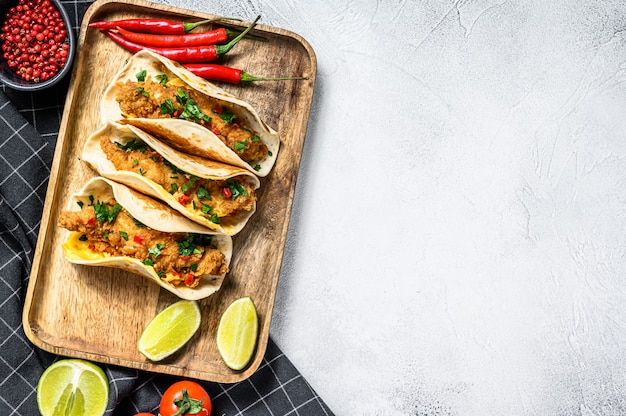 Traditional mexican tacos with parsley, cheese and chili peppers. white background.