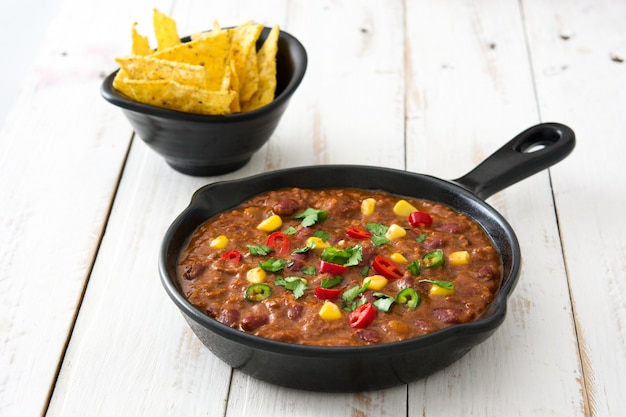 Traditional mexican tex mex chili con carne in a frying pan on white wooden table