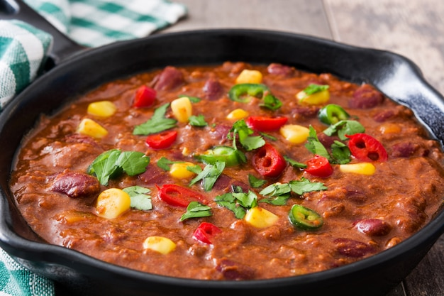 Traditional mexican tex mex chili con carne in a frying pan on wooden table close up