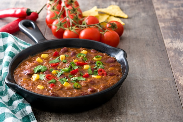 Traditional mexican tex mex chili con carne in a frying pan on wooden table copy space