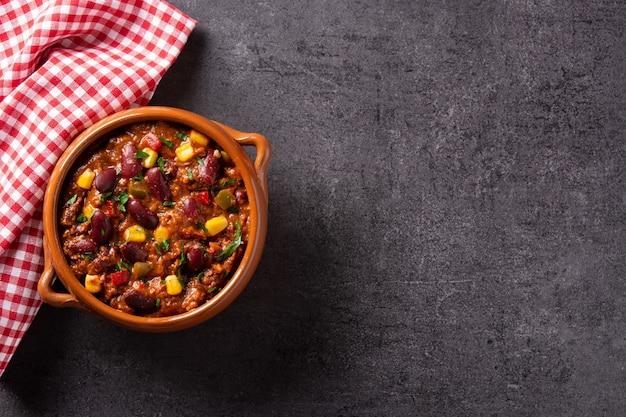 Традиционный мексиканский текс mex chili con carne в миске на черном фоне.