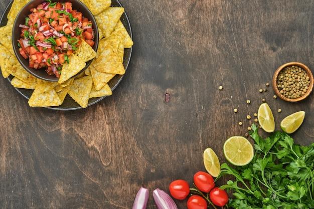 나초와 재료 토마토, 칠레, 마늘, 양파를 어두운 오래된 나무 배경에 넣은 전통적인 멕시코 토마토 소스 살사. 라틴 아메리카와 멕시코 음식의 개념입니다. 조롱.