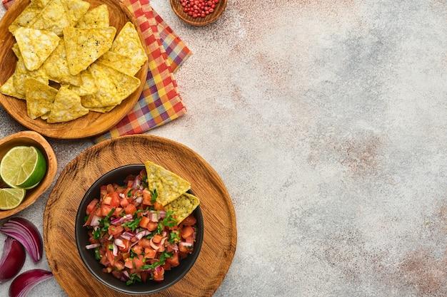 나초와 재료 토마토, 칠레, 마늘, 양파를 밝은 슬레이트 돌 배경에 넣은 전통적인 멕시코 토마토 소스 살사. 라틴 아메리카와 멕시코 음식의 개념입니다. 조롱.