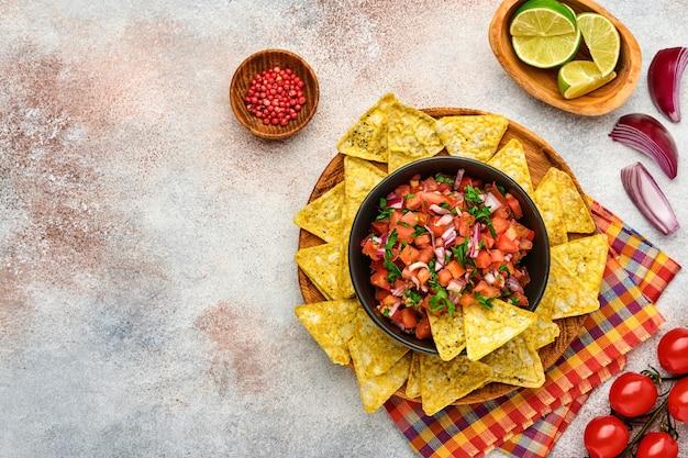 Традиционный мексиканский томатный соус сальса с начос и ингредиентами, помидорами, чили, чесноком, луком на светлом фоне сланцевого камня. концепция латиноамериканской и мексиканской кухни. макет.
