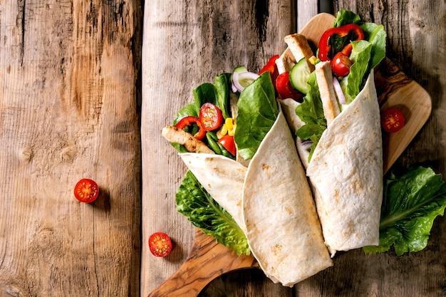 Традиционный мексиканский оберток из тортилы со свининой и овощами на деревянной разделочной доске над коричневой деревянной поверхностью. вид сверху, плоская планировка. скопируйте пространство. домашний фастфуд
