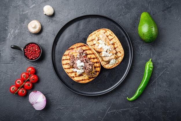 食材のミックスと伝統的なメキシコのトルティーヤ、黒の背景に黒のプレートの側
