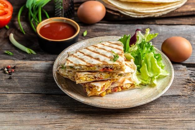 スクランブルエッグ、野菜、ハム、チーズを添えたケサディーヤトルティーヤを添えた伝統的なメキシコのトルティーヤ