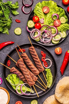 Traditional middle eastern arabic or mediterranean meat kebab with vegetables and pita bread