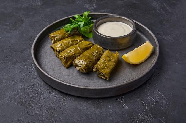 伝統的な中東料理のドルマまたはサルマとパセリ鍋、サワークリームとレモン