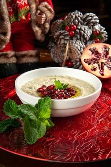 전통적인 중동 음식. 레바논 음식. 석류 씨앗과 크리스마스 장식이있는 아라비아 바바가 누스