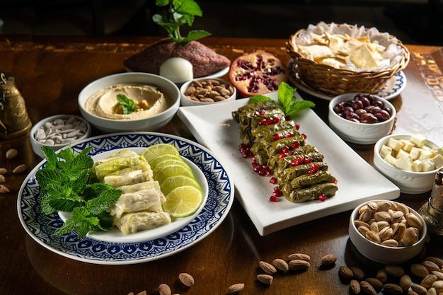 伝統的な中東料理。レバノン料理。ザクロの種、フムス、キャベツのマルフフ、生のキッベを添えたアラビアのブドウの葉の詰め物