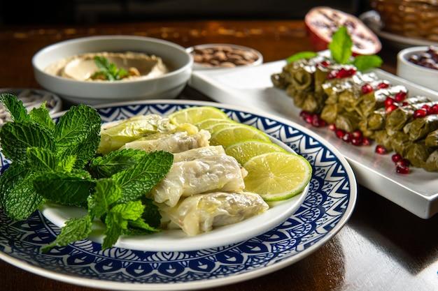 伝統的な中東料理。レバノン料理。ザクロの種子、フムス、キャベツのマルフフとアラビアのぬいぐるみブドウの葉