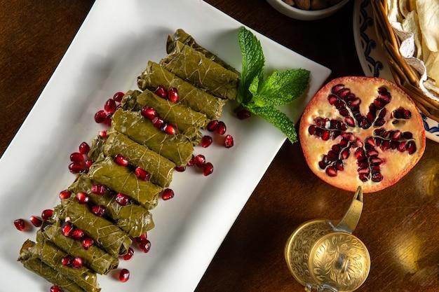 伝統的な中東料理。レバノン料理。ザクロの種子とアラビアのぬいぐるみブドウの葉、上面図