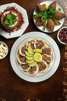 伝統的な中東料理。レバノンのエスフィーハ肉。アラビアのエスフィーハプレート。レモンとエスフィーハ。キッベキベ。上面図