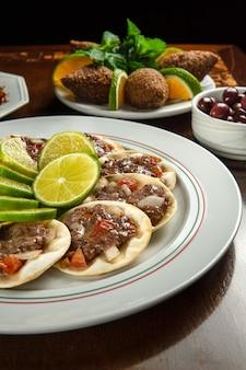 伝統的な中東料理。レバノンのエスフィーハ肉。アラビアのエスフィーハプレート。レモンとエスフィーハ。 kibbeh kibe