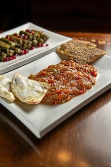 伝統的な中東料理。レバノンのブドウの葉の詰め物。アラビア料理。茄子とトマト、マナイーシ