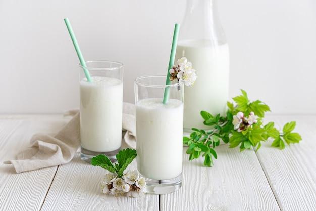 Традиционный молочный напиток на белой стене с зеленью и цветами