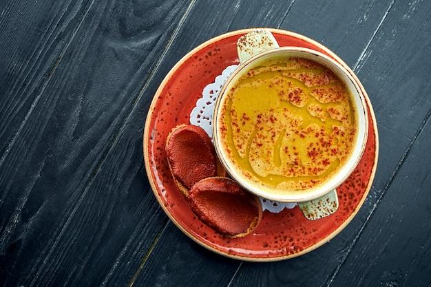 伝統的なモロッコのスープ-ハリラ、黒い木の表面の赤いプレートにコリアンダーが入った黄色いレンズ豆のスープ。ダイエットスープ