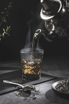 Traditional moroccan teapot pouring tea into a steaming glass with natural tea and mint