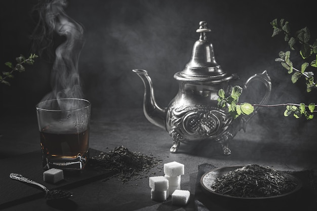 Traditional moroccan teapot, with a steaming cup of tea, sugar and mint