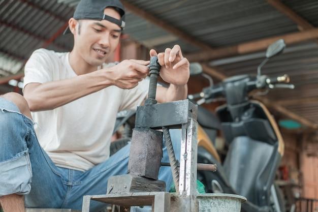 インドネシアでの伝統的なモーターサイクルタイヤの修理