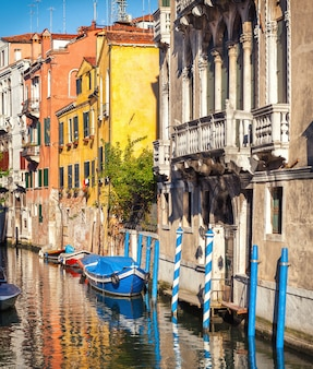Traditional narrow canal in venice, italy. medieval old buildings with a renaissance balcony.