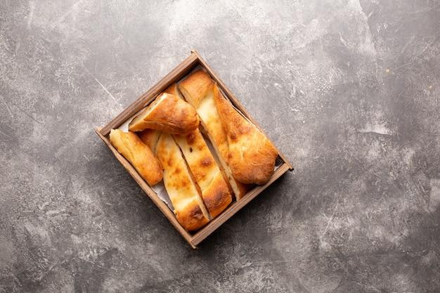 伝統的な国のグルジアのショティパン。スライスされたパンは、灰色のコンクリートの木製の箱の中にあります。上面図。