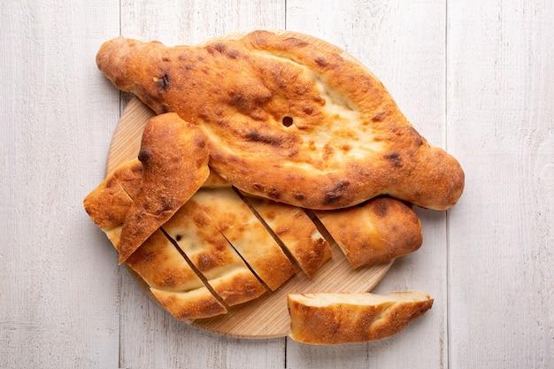 伝統的な国のグルジアのショティパン。スライスされたパン全体が白い木のまな板の上にあります。上面図。
