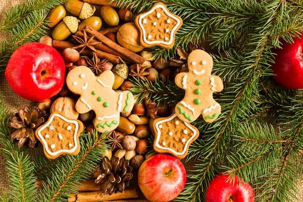 빨간 사과, 견과류, 계피 스틱, 생강 쿠키가 있는 전통적인 새해 배경. 가문비나무 가지와 원뿔. 평면도.