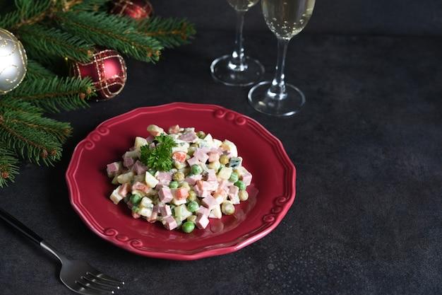 Традиционный новогодний салат оливье. новогодний праздничный стол и бокалы шампанского.