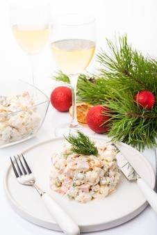 흰색 배경에 축제 장식이 있는 전통적인 새해 샐러드 올리비에, 클로즈업