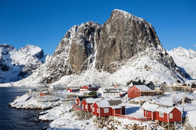 피요르드와 멀리 산 기슭에 서 있는 전통적인 노르웨이 목조 주택 로부. 로포텐 제도. 노르웨이. 세계 여행