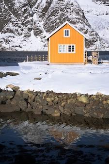 피요르드와 멀리 산 기슭에 서 있는 전통적인 노르웨이 목조 주택 로부. 로포텐 제도. 노르웨이.