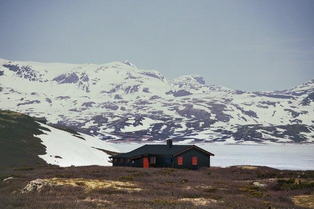 Традиционный норвежский деревянный дом на берегу озера и в горах вдали, норвегия