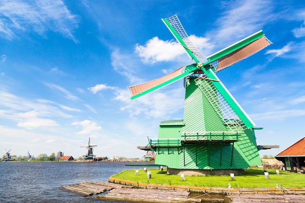 Traditional old dutch windmill against blue cloudy sky in the zaanse schans village, netherlands.