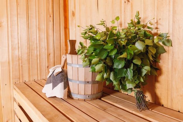 Традиционная старая русская баня spa concept. детали интерьера финская сауна парная с традиционными принадлежностями для сауны умывальник березовый веник совок войлок. расслабьтесь в деревенской бане.