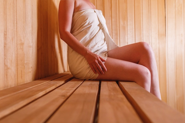 전통적인 핀란드식 사우나에서 수건으로 휴식을 취하는 전통적인 러시아식 목욕탕 스파 컨셉의 여성입니다.