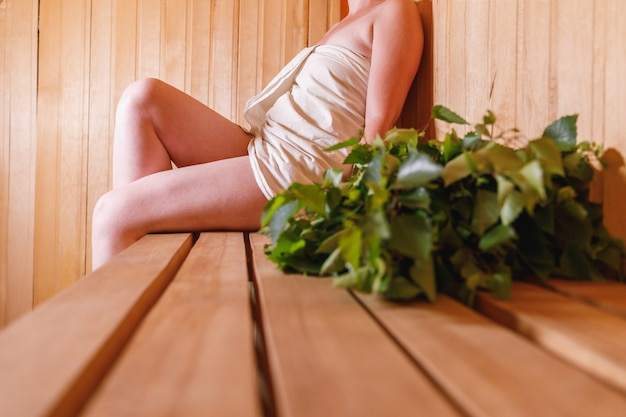 Traditional old russian bathhouse spa concept woman relaxing in finnish sauna interior steam room wi...
