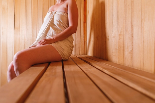 Traditional old russian bathhouse spa concept. woman in towel relaxing in traditional finnish sauna interior steam room. relax country village bath concept.