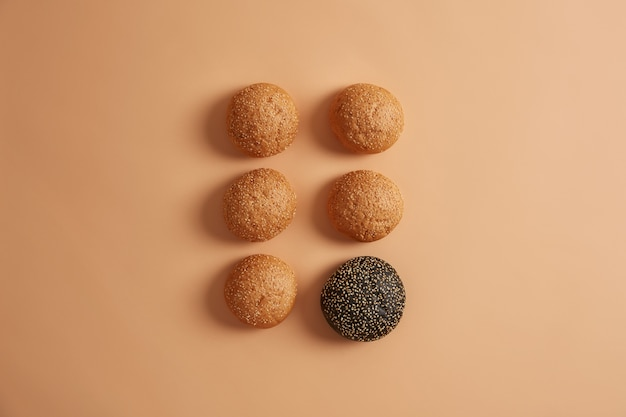 Traditional and one black cuttlefish ink burger buns with sesame seeds without adding arranged in two rows, isolated on beige background. homemade hamburger bread. unhealthy street food concept