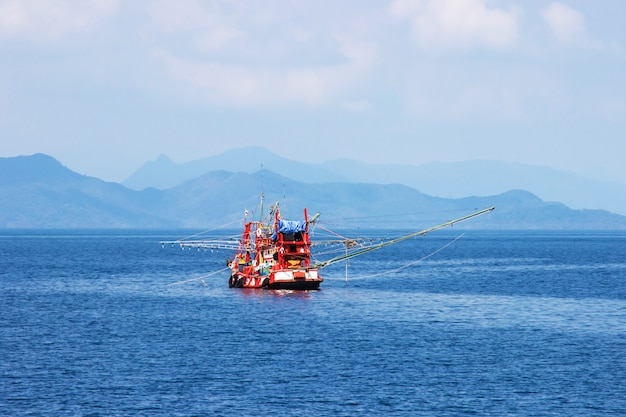 Traditional orange thai fishing boat floating in the bay of thailand near koh chang on day the bright sky.