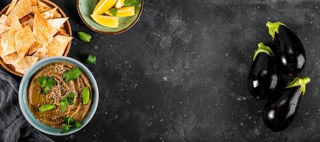 참깨와 민트 잎 클로즈업으로 전통적인 동양 전채 baba ganoush. 피타 칩을 곁들인 가지 후 무스.