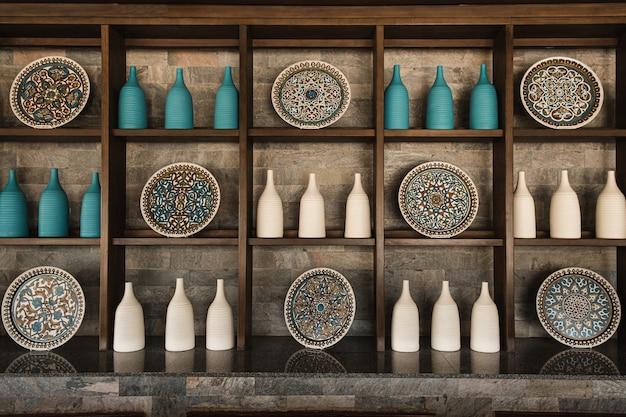 Традиционный восточный дизайн интерьера бара с деревянной мебелью, бутылками, декоративными тарелками